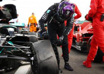 Pebalap Mercedes Lewis Hamilton memeriksa ban mobilnya yang pecah jelang finis Grand Prix Britania, Sirkuit Silverstone, Inggris, Minggu (2/8/2020) (Pool via REUTERS/BRYN LENNON)