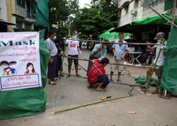 Para pria membangun brikade yang memblokir jalan mereka untuk mencegah penyebaran Covid-19 di Yangon, Myanmar, (12/09/2020) – (Sumber Foto: Shwe Paw Mya Tin-Reuters).