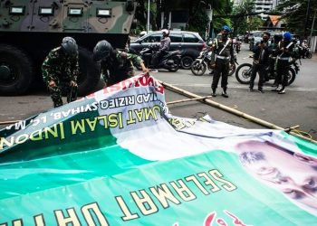 Tampak Prajurit TNI menurunkan Baliho HRS atas Perintah Pangdam Jaya